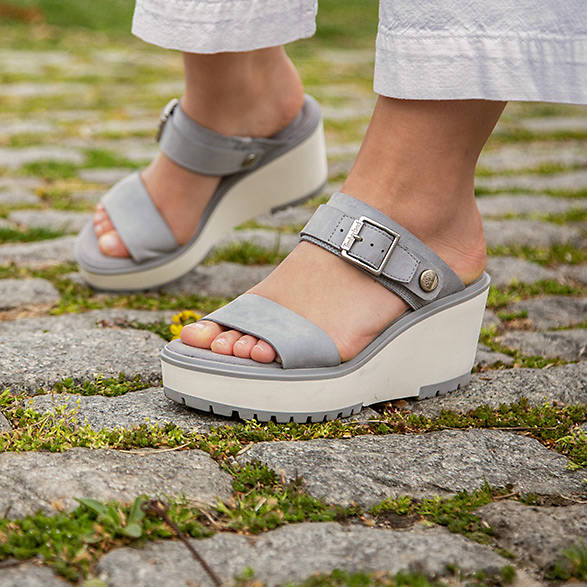 sandales grises à semelle compensée pour femmes sur des pierres