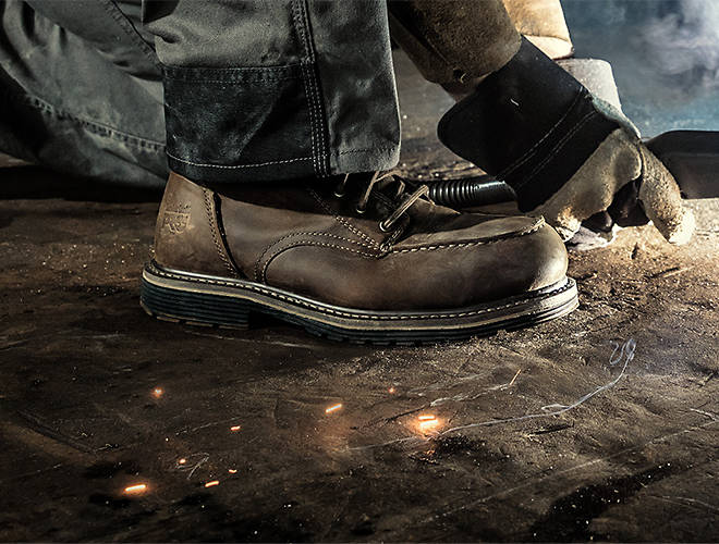 A welder with brown work boots on