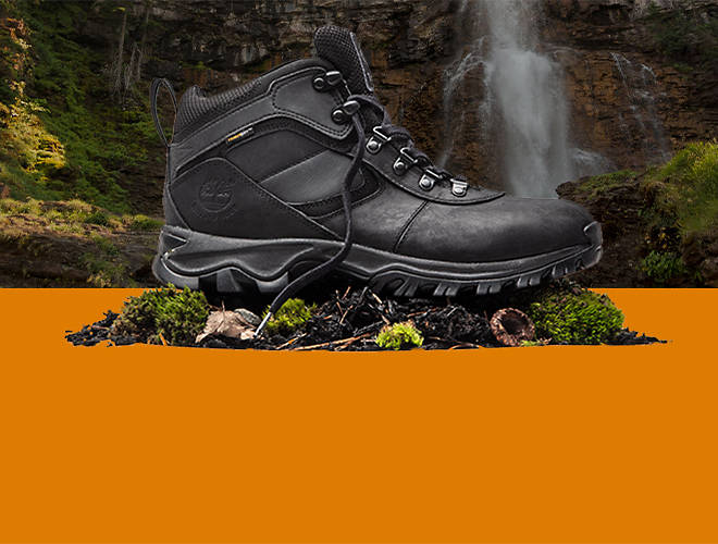 A black hiking boot with a waterfall behind it