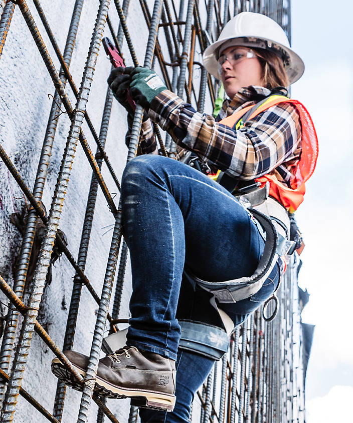 woman climbing scaffolding in boots